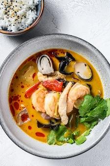 Tom yum suppe mit garnelen und kokosmilch. grauer hintergrund. draufsicht