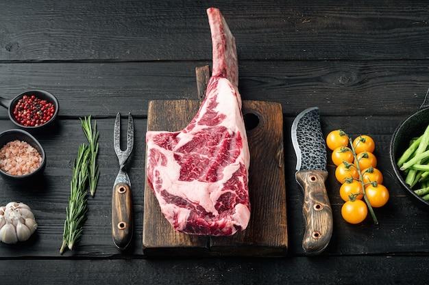 Tomahawk rohes frisches rindfleischsteak mit gewürzen, mit grillzutaten, auf schwarzem holztisch tisch