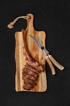 Tomahawk-steak in scheiben geschnitten auf holzbrett