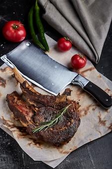 Tomahawk steak mit gemüse und einem messer auf dem tisch. gegrilltes fleisch mit gegrilltem gemüse und frischem gemüse auf dem tisch.