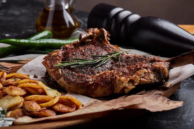 Tomahawk-steak mit gemüse und einem messer auf dem tisch. gegrilltes fleisch mit gegrilltem gemüse und frischgemüse auf dem tisch.