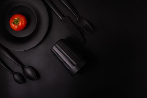 Tomate auf einem schwarzen hintergrund mit schwarzem tischbesteck, draufsicht