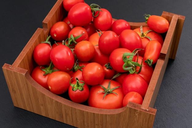 Tomate in der holzkiste auf schwarzer steinoberfläche