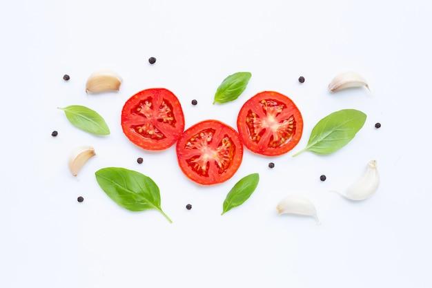 Tomate, knoblauch, pfefferkorn und basilikum getrennt auf weiß