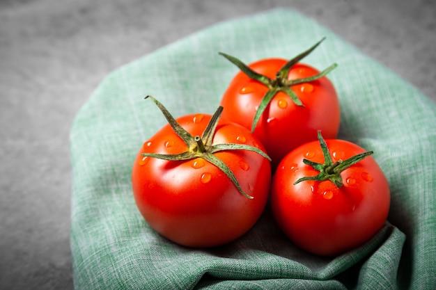 Tomate mit tropfen. volle schärfentiefe. frische rote reife tomaten zur verwendung als kochzutaten im vordergrund mit copyspace auf dunklem hintergrund. tomaten ernten. draufsicht