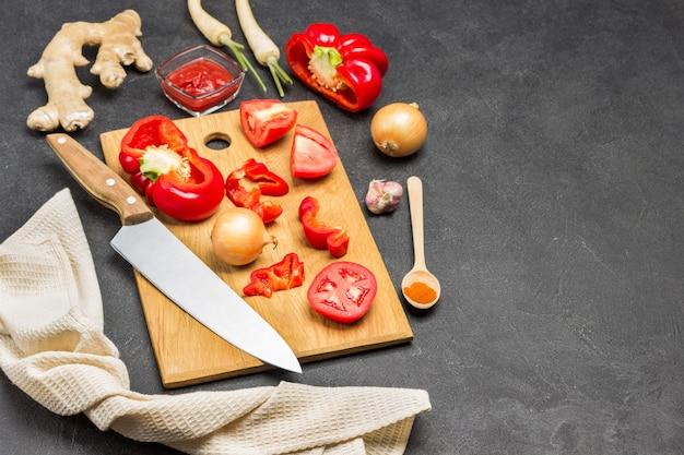 Tomate, paprika und messer auf schneidebrett. beige serviette. ingwerwurzel, zwiebel und löffel auf dem tisch. platz kopieren. schwarzer hintergrund. ansicht von oben