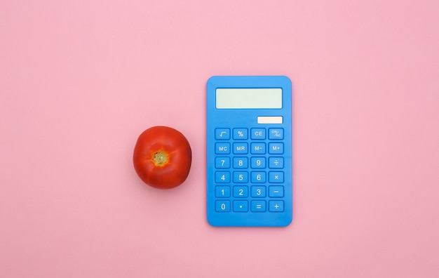 Tomate und taschenrechner auf rosa pastellhintergrund. flache zusammensetzung.