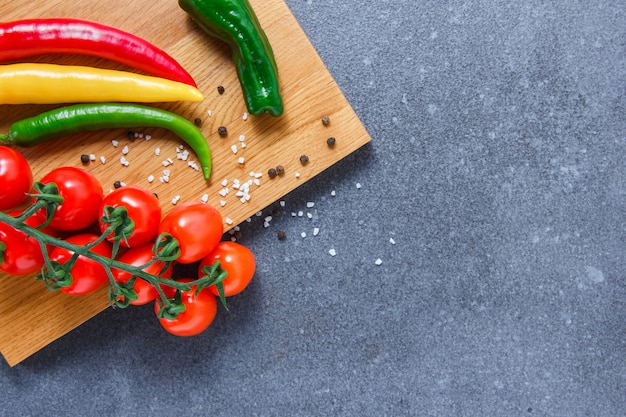 Tomaten auf einem schneidebrett mit pfeffer draufsicht auf einem grauen strukturierten hintergrund freien raum für ihren text