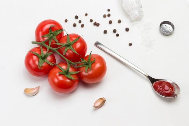 Tomaten auf grünem zweig. knoblauch, salz und piment auf dem tisch.