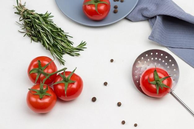 Tomaten auf grünem zweig. tomate und piment auf grauem teller. tomate mit grünem schwanz am abschäumer. graue serviette. weißer hintergrund. flach liegen