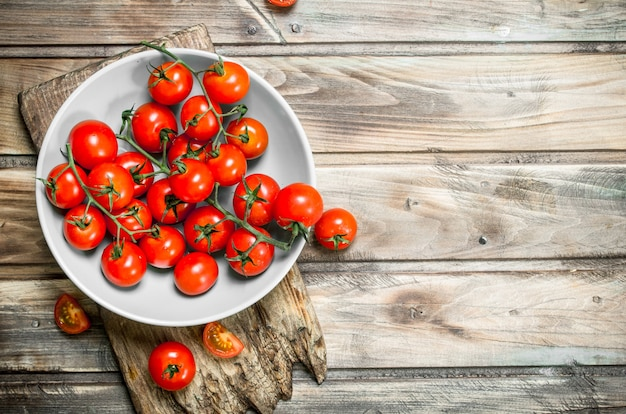 Tomaten auf teller auf schneidebrett auf holztisch