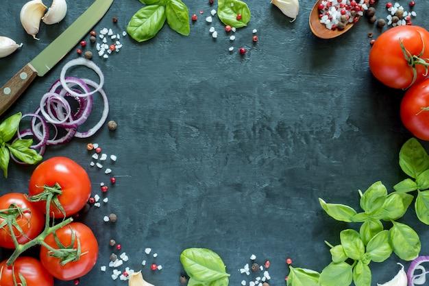 Tomaten-basilikum-knoblauch und gewürze auf einer steintabelle. das konzept des kochens. draufsicht mit platz für text