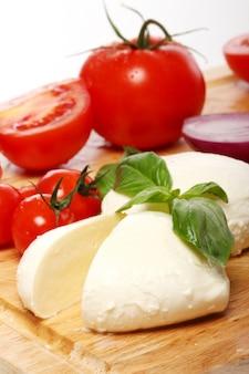 Tomaten, basilikum und mozzarella auf holzbrett
