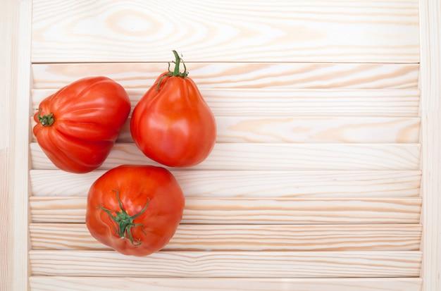Tomaten coeur de boeuf auf hölzernem hintergrund. draufsicht