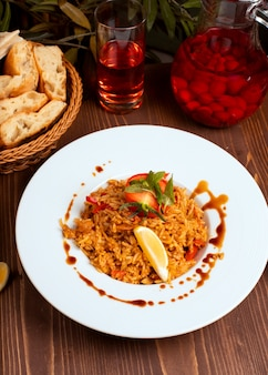Tomaten-currysauce-risotto mit kräutern und gemüse, zitrone.