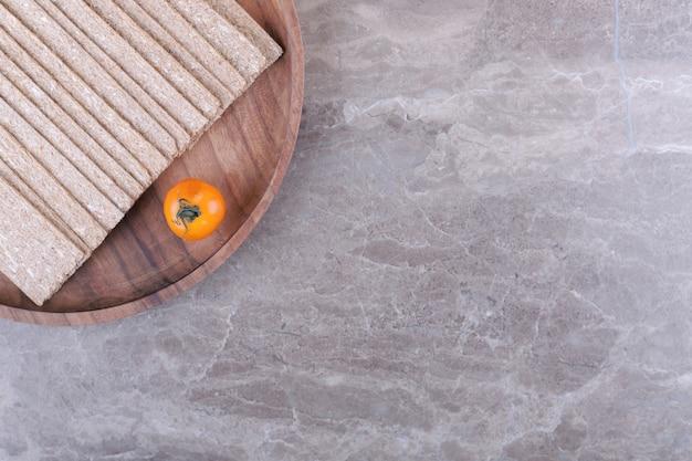 Tomaten ein stapel knäckebrot auf dem holzbrett, auf dem marmorhintergrund.
