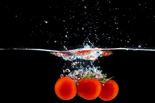 Tomaten fallen mit einem spritzer gegen schwarz ins wasser
