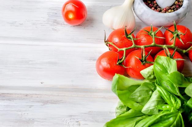 Tomaten, grünes basilikum und gewürze in einem steinmörser,