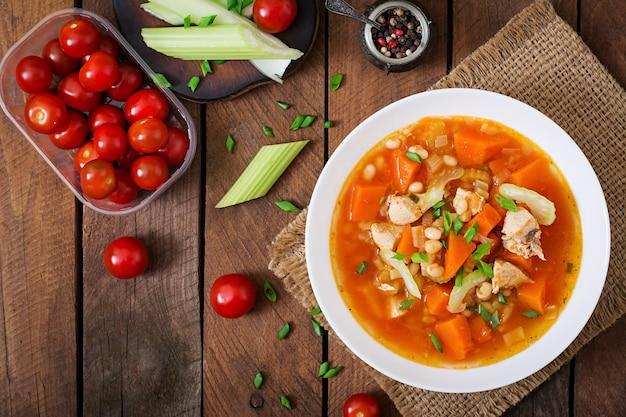 Tomaten-hühnersuppe mit kürbis, bohnen und sellerie in weißer schüssel. draufsicht