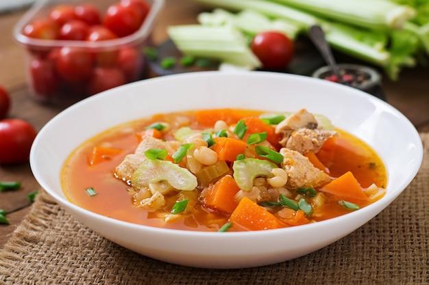 Tomaten-hühnersuppe mit kürbis, bohnen und sellerie in weißer schüssel