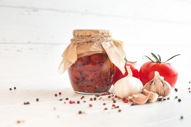 Tomaten im glas. hausgemachte sonnengetrocknete tomaten. vorübergehende schließung. sommer- und herbstkonserven. mit gewürzen und gemüse konservieren.