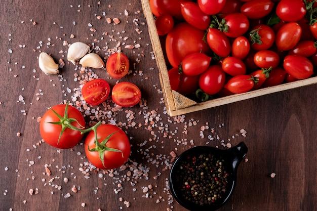 Tomaten in der holzkiste nahe dem pulver des schwarzen pfeffers im schwarzen schüsselknoblauch und tomaten verbreiteten seesalz auf brauner steinoberflächenhahnansicht