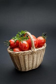 Tomaten in einem weidenkorb auf grauer oberfläche