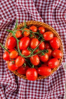 Tomaten in einem weidenkorb auf picknicktuch, draufsicht.