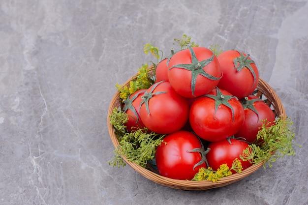 Tomaten in einer holzschale mit kräutern herum.