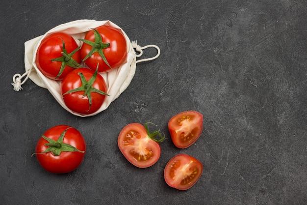 Tomaten in wiederverwendbarem netzbeutel. ganze tomaten und gehackte tomatenschnitze auf dem tisch. schwarzer hintergrund. draufsicht. speicherplatz kopieren
