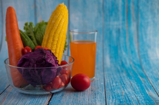 Tomaten, karotten, gurken, zwiebeln, salate und purpurkohl in einer glasschale. und orangensaft.