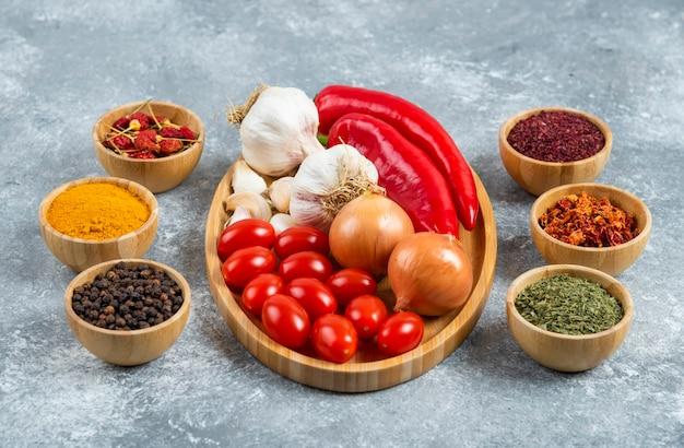 Tomaten, knoblauch und paprika auf holzteller mit gewürzen.