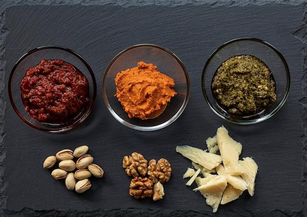 Tomaten-mascarpone-sauce, parmesan, harissa-paste, nüsse und pesto-sauce auf dunklem schieferkäsebrett