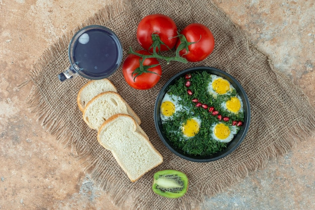 Tomaten mit brot und eine tasse tee mit omelett.