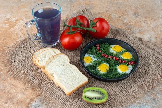Tomaten mit brot und eine tasse tee mit omelett