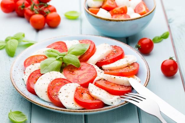 Tomaten, mozzarella, basilikum und gewürze auf grauer schiefersteintafel. italienische traditionelle caprese-salatzutaten. mediterranes essen.