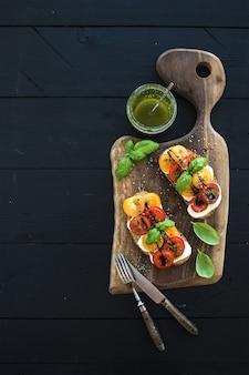 Tomaten-, mozzarella- und basilikumsandwiche auf dunklem hölzernem schneidebrett, pestoglas, essgeschirr