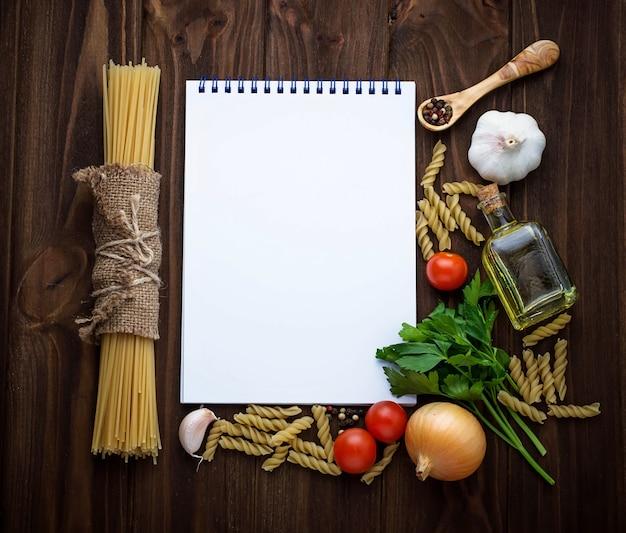 Tomaten, nudeln, knoblauch, petersilie und leeres notizbuch