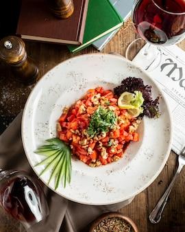 Tomaten-nuss-salat mit zitronenscheibe