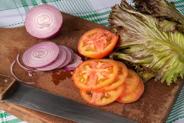 Tomaten, rote zwiebeln und roter salat im detail auf holz über karierter tischdecke