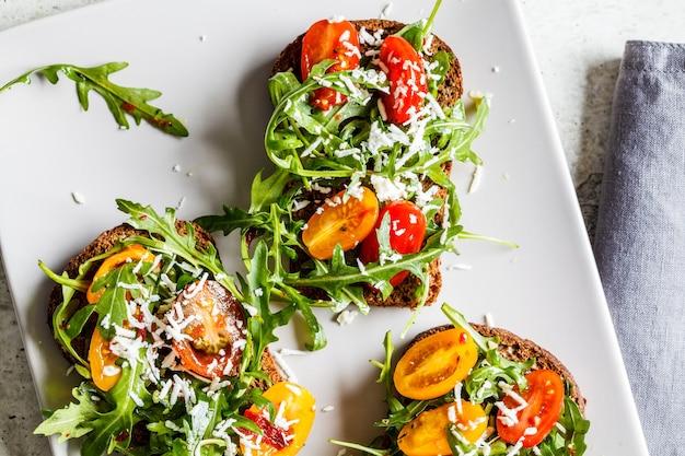 Tomaten-, rucola- und käsesandwiches auf einem grauen teller, draufsicht.