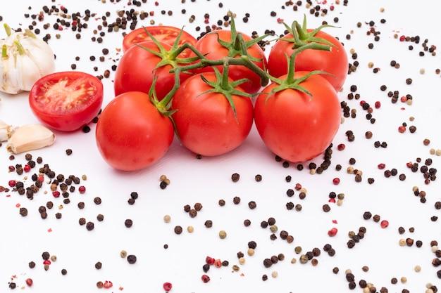 Tomaten umgeben durch schwarzen und roten pfeffer und knoblauch auf weißer oberfläche
