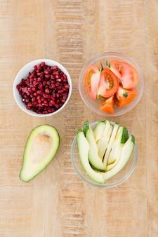 Tomaten- und avocado-scheiben mit granatapfelkernen in schalen auf dem tisch