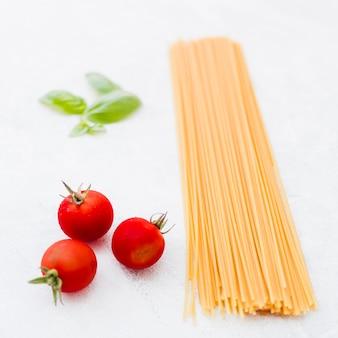 Tomaten und basilikumblätter mit rohen spaghettis auf weißem hintergrund