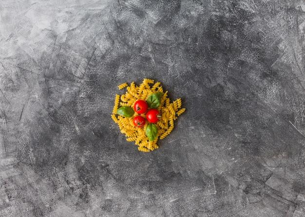 Tomaten und basilikumblätter über den rohen fusilli auf schmutzigem fleckhintergrund