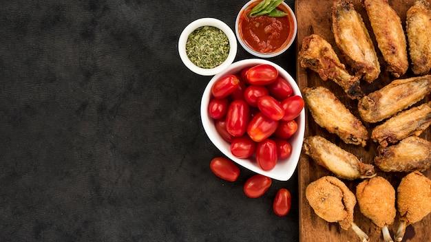 Tomaten und gewürze in der nähe von brathähnchen