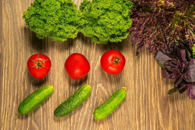 Tomaten und gurken auf einem alten holztisch. das konzept einer gesunden ernährung. gemüse für salat.