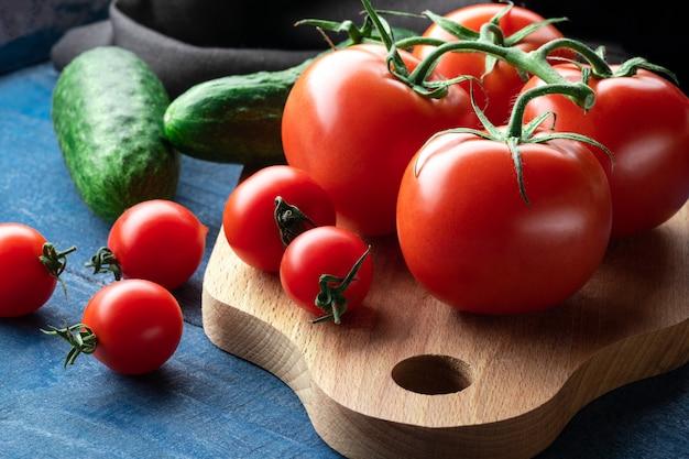 Tomaten und gurken auf holzbrett mit rohen nudeln auf blauem hintergrund. nahaufnahme