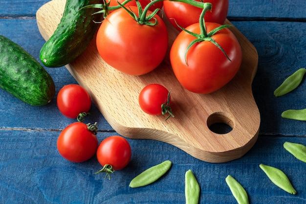 Tomaten und gurken auf holzbrett mit rohen nudeln auf blauem hintergrund