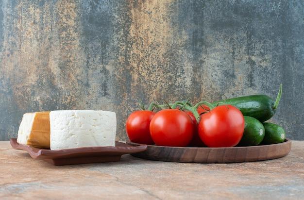 Tomaten und gurken mit käse auf marmor